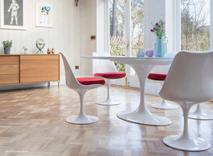 white tulip side chairs with red cushions and wooden flooring