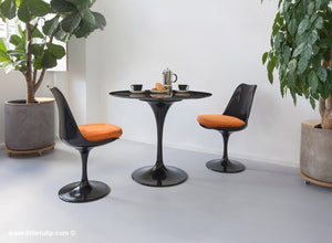 The 90cm TUlip dining set is so versatile and the two chairs come with orange cushions