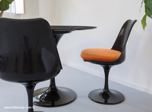 The wonderful back Tulip Table and Tulip Chair sets come here with orange cushions