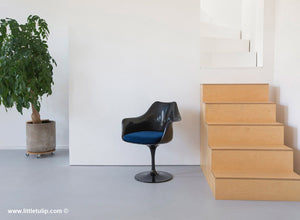 The Saarinen Tulip Arm Chair in black with a matching blue cushion