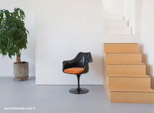 The Saarinen Tulip Arm Chair in black with a matching orange cushion