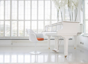 Tulip Arm Chair with orange cushion and white Grand Piano