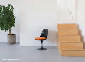 The Saarinen Tulip Side Chair in black with a orange cushion