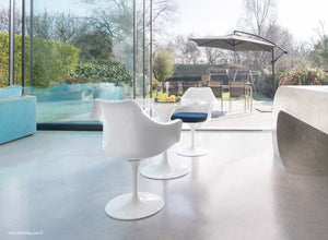 Garden view of marble tulip table and arm chairs with blue cushions