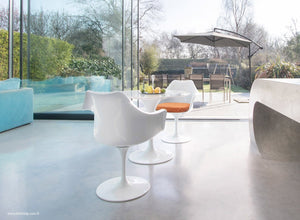 Garden view of marble tulip table and arm chairs with orange cushions