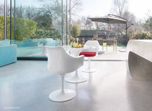 Garden view of marble tulip table and arm chairs with red cushions