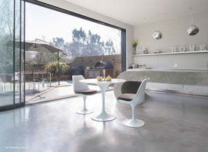 Room view of small marble tulip table and tulip chairs in grey