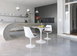 Grey cushions on tulip side chairs and table by a breakfast bar