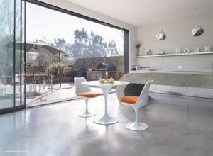 Room view of small marble tulip table and tulip chairs in orange
