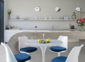 Close up view of marble Tulip Table and chairs with blue cushions