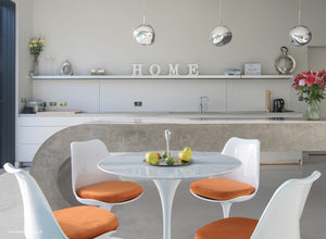 Close up view of marble Tulip Table and chairs with orange cushions