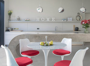 Close up view of marble Tulip Table and chairs with red cushions