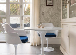 Main view of tulip arm chair with blue cushions and small round tulip table