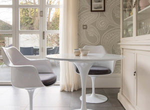 Main view of tulip arm chair with grey cushions and small round tulip table