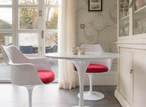 Main view of tulip arm chair with red cushions and small round tulip table