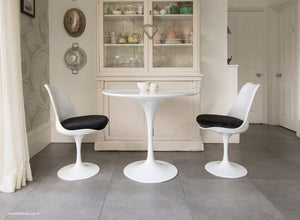 Kitchen table with black cushioned tulip chairs