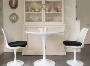 Main view of 90cm white tulip table with two chairs with black cushions