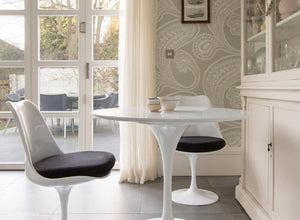 Side view of a small round tulip table & 2 tulip chairs in black