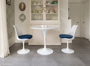 Kitchen table with blue cushioned tulip chairs