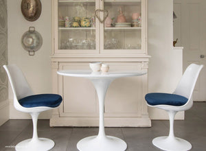 Main view of 90cm white tulip table with two chairs with blue cushions