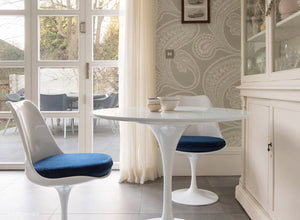Side view of a small round tulip table & 2 tulip chairs in blue