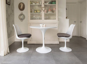 Kitchen table with grey cushioned tulip chairs