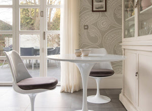 Side view of a small round tulip table & 2 tulip chairs in grey