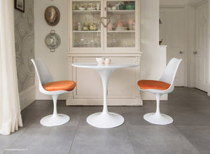Kitchen table with orange cushioned tulip chairs
