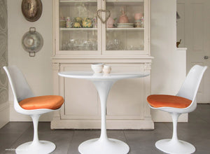 Main view of 90cm white tulip table with two chairs with orange cushions