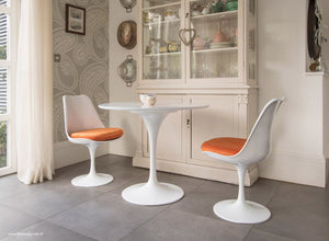 Side view of small tulip dining set with orange cushions