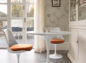 Side view of a small round tulip table & 2 tulip chairs in orange