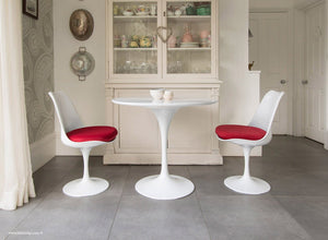 Kitchen table with red cushioned tulip chairs