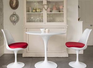 Main view of 90cm white tulip table with two chairs with red cushions