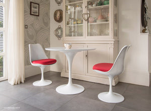 Side view of small tulip dining set with red cushions