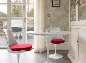 Side view of a small round tulip table & 2 tulip chairs in red