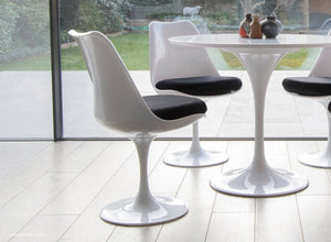 Tulip Chair with black cushion shown with bi-folding modern doors
