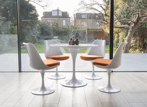 Tulip table and chair set in orange shown in a modern kitchen