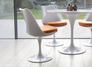Tulip Chair with orange cushion shown with bi-folding modern doors
