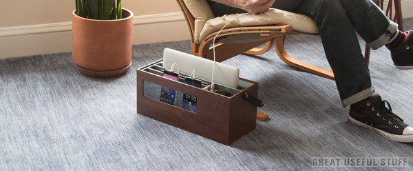 Walnut wood charging station resting on carpet in living room next to designer recliner where man uses phone while it charges