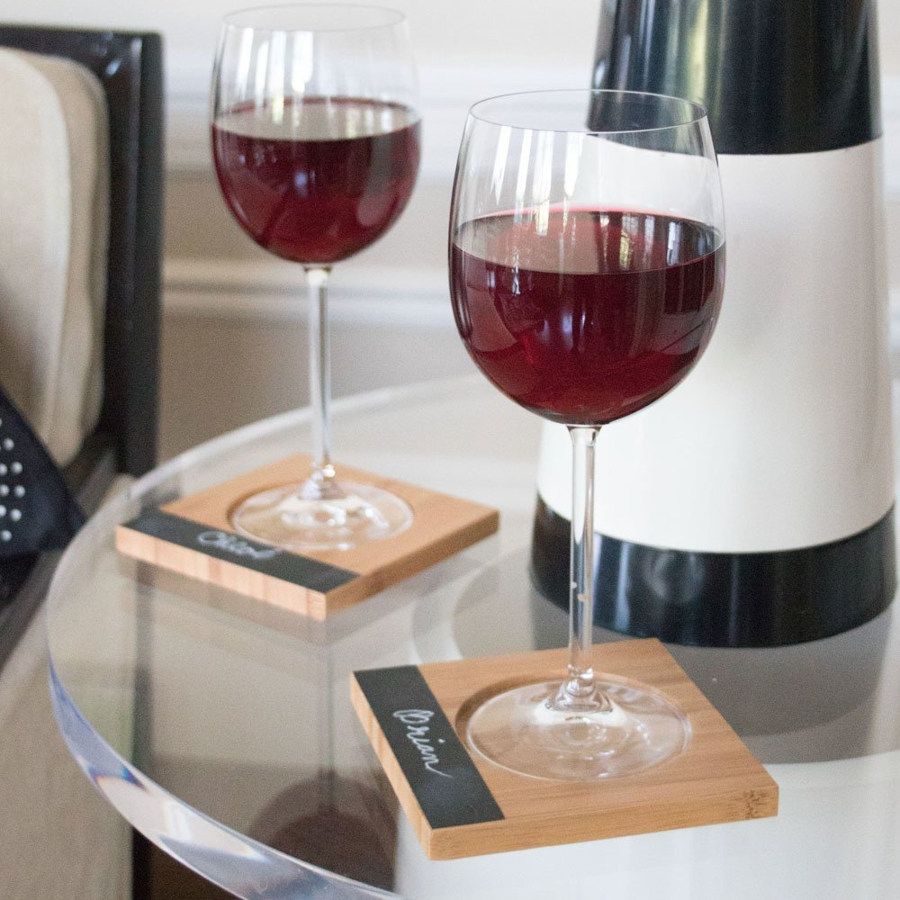 Two glasses of red wine on bamboo coasters on lucite table for guests