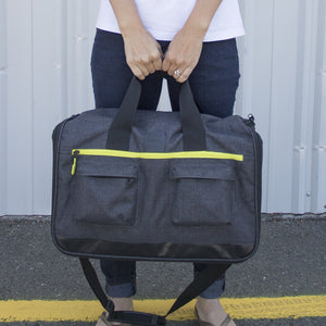 person holding weekender bag by short carry handles