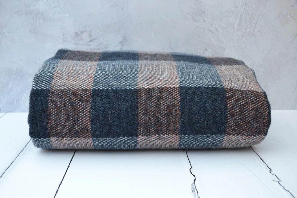 A large super soft and warm traditional Welsh blanket that is finished with a blanket stitch hem. Traditionally woven in Wales. A Blue and Cream warp in a multi colour check of subtle Burnt Orange.