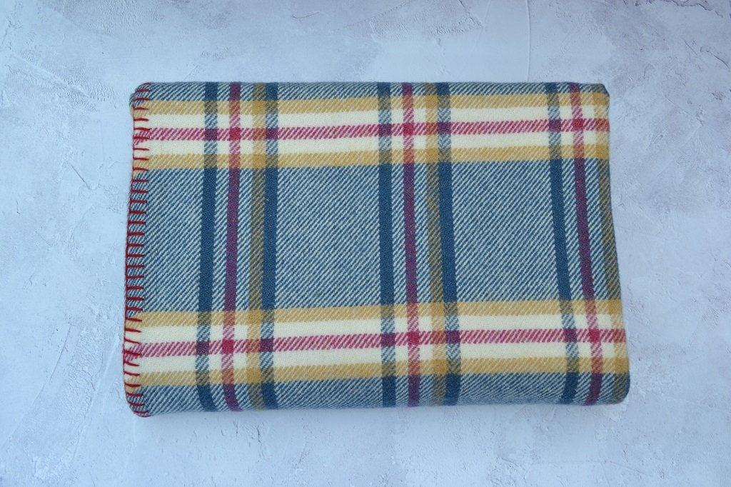 Traditional Welsh wool throw finished with a blanket stitch hem. Blue and Cream warp with a Fuchsia and Mustard check pattern