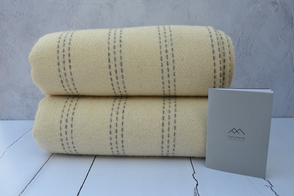 Welsh blankets for sale - The Cilmeri blanket is woven in Welsh Mule fleece.  Woven in a corded rib design to give texture to the blanket with a simple broken single strand stripe in Jacob natural grey. Finished with a blanket stitch