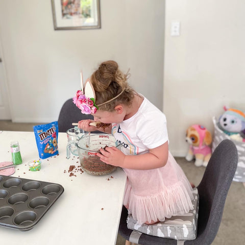 Annabelle making chocolate Easter eggs with her Minene booster cushion