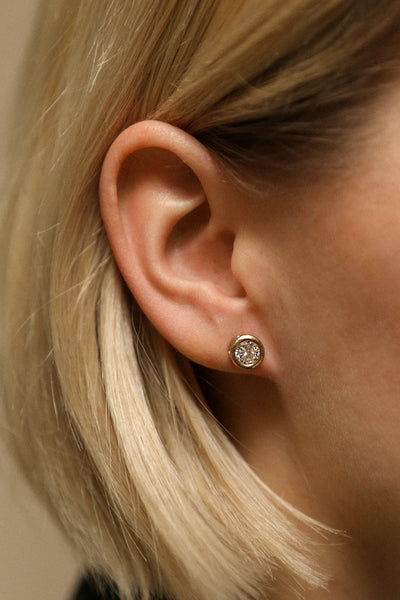 Arie Wolke - Golden and clear crystal stud earrings on blond model