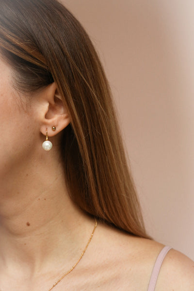 Azerro Gold Pearl Pendant Earrings | La Petite Garçonne on model with brown hair