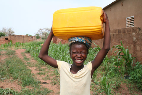 African Girl Carrying water on head from the river