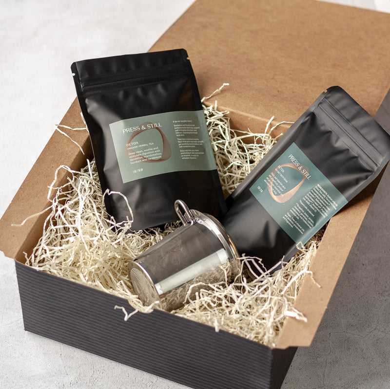 Detox gift set featuring Detox sea salt bath salts and organic herbal tea, and a stainless steel fine mesh infuser (in a black kraft box).