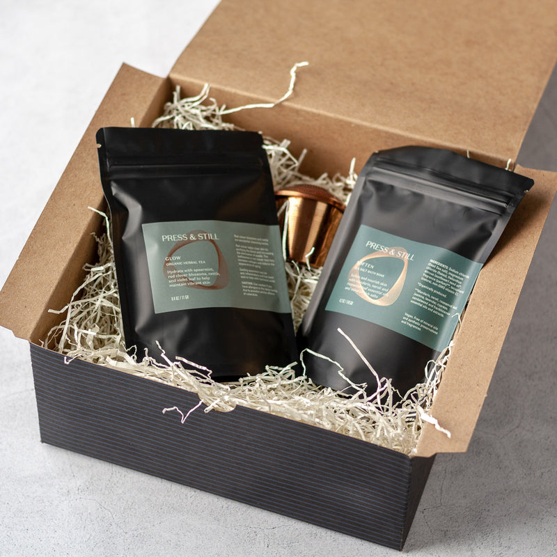 Glow gift set featuring Glow organic herbal tea, Soften bath soak and a rose gold-colored tea infuser..
